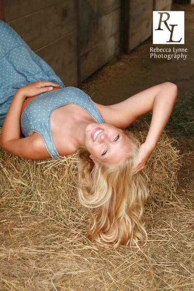 Senior girl high school portrait lay in hay cowgirl