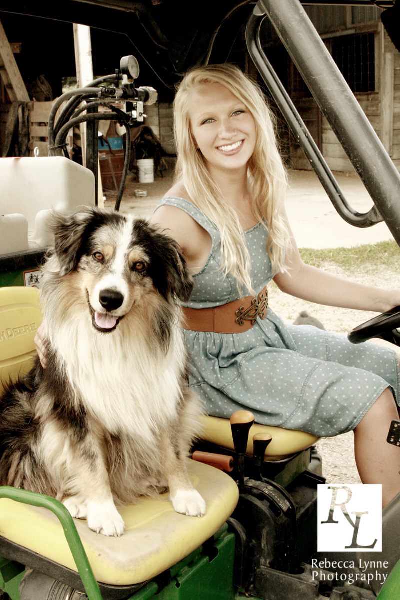 Senior girl high school portrait riding with dog john deere
