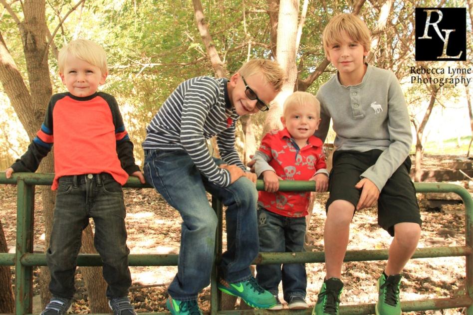 four boys climb fence